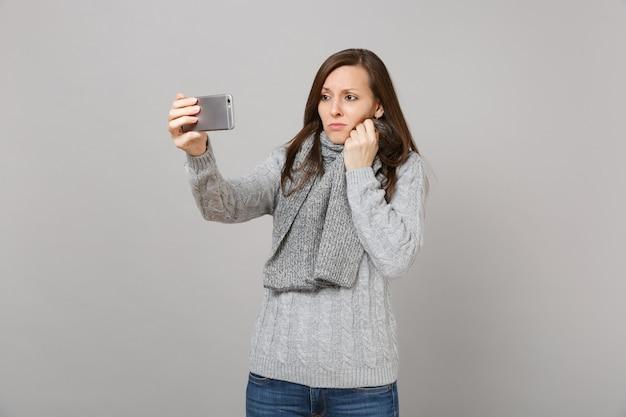 Boos jonge vrouw in trui, sjaal doen selfie schot op mobiele telefoon, video-oproep maken geïsoleerd op een grijze achtergrond. gezonde mode levensstijl mensen emoties koude seizoen concept. bespotten kopie ruimte.