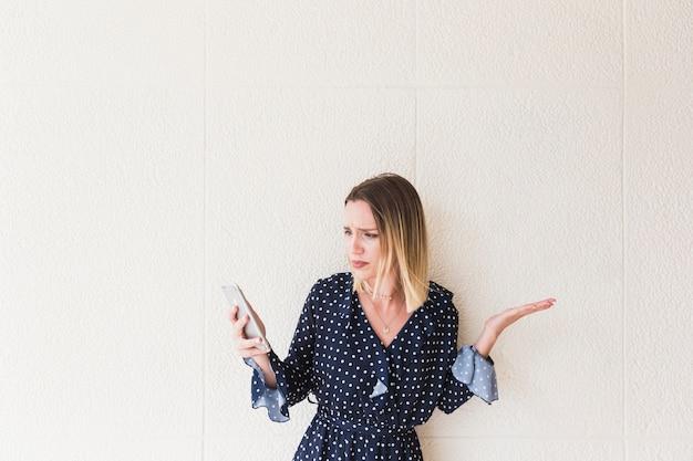 Boos jonge vrouw kijken naar mobiele telefoon schouderophalend
