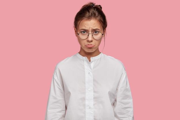 Boos jonge vrouw met bril poseren tegen de roze muur