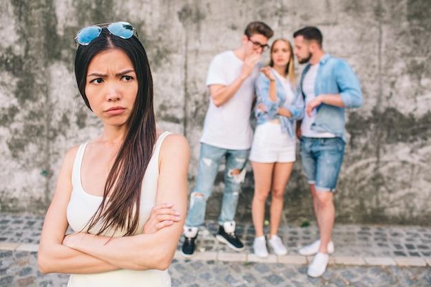 Boos jonge vrouw staat ver van haar vrienden