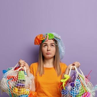 Boos jonge vrouwen poseren met vuilnis op hen