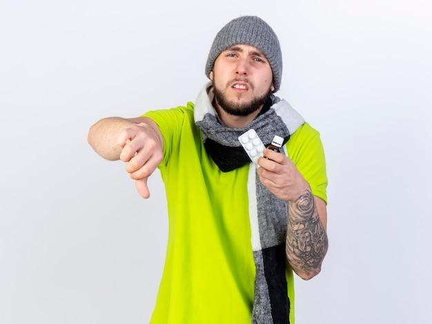 Boos jonge zieke man met winter hoed en sjaal duimen naar beneden en houdt medicijnen in een glazen fles en een pakje medische tabletten geïsoleerd op een witte muur