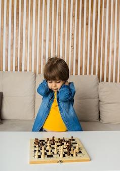Boos jongetje zit in een kamer en speelt schaak