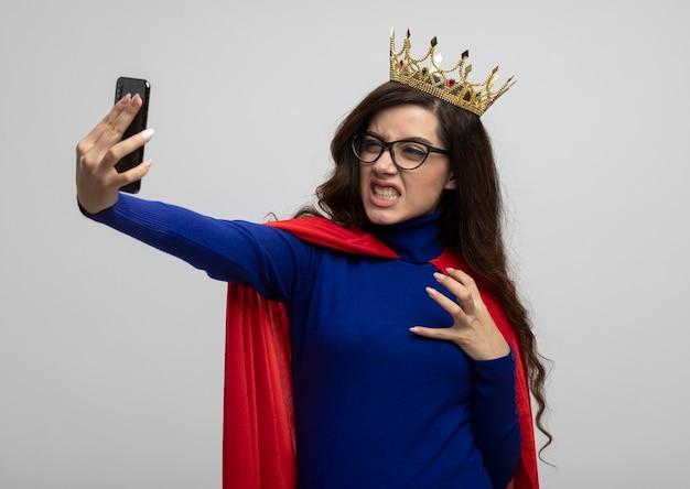 Boos kaukasisch superheld meisje met kroon en rode cape in optische glazen gebaren tijger poot houden