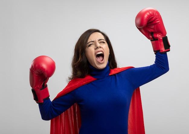Boos kaukasisch superheldmeisje met rode cape die het dragen van bokshandschoenen staat met opgeheven handen