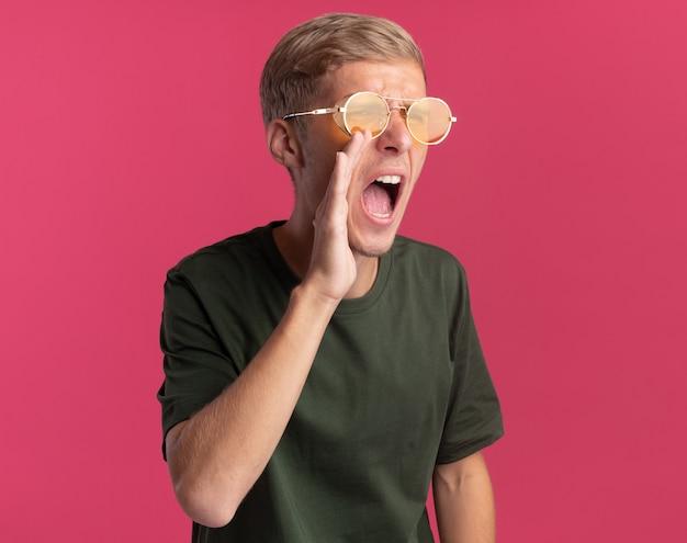 Boos kijken naar kant jonge knappe kerel die een groen overhemd en een bril draagt en iemand belt die op roze muur wordt geïsoleerd