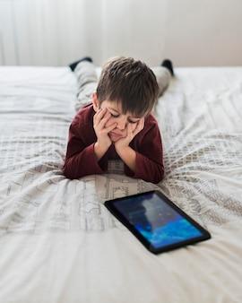 Boos kind in bed met tablet