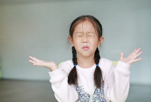 Boos klein aziatisch kindmeisje in klaslokaal. niet aan het luisteren. teken en gebaar concept.