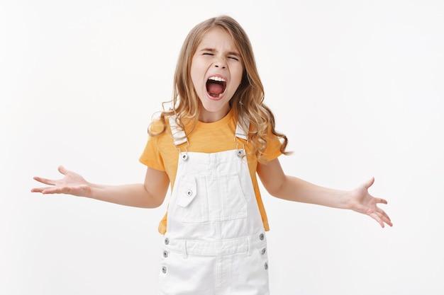 Boos klein kind, meisje dat hardop schreeuwt, zich misdraagt, ruzie maakt haat iedereen staat pissig geïrriteerd oneerlijke behandeling, jammerend slecht humeur tonend, humeurig tegen de witte muur staan