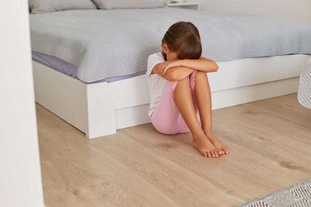 Boos klein kindmeisje huilend zittend alleen op de vloer, zittend in de buurt van bed met haar hoofd naar beneden, verdrietig eenzaam kind dat wordt gepest, misbruikt, zich gestrest of bang voelt, geweld door kinderen.