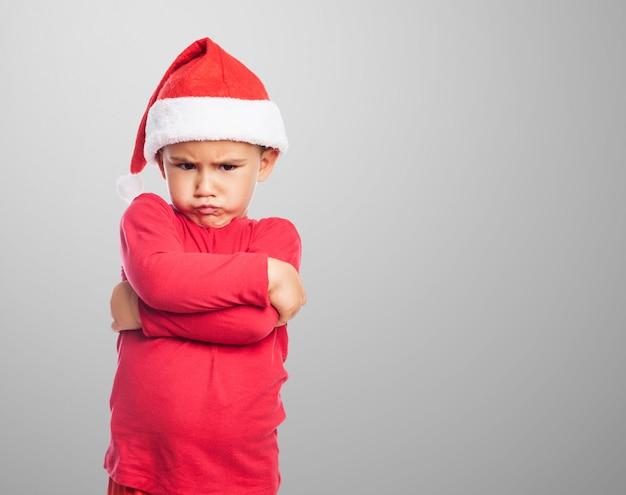 Boos kleine jongen met kerst man hoed