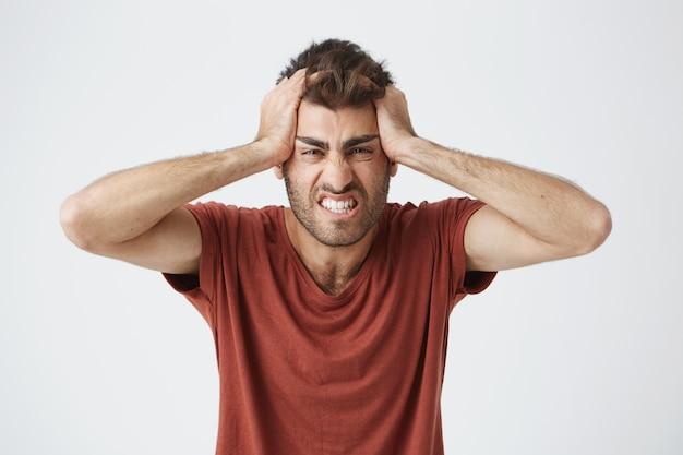 Boos knappe blanke man in rood t-shirt met gekke uitdrukkingen, hoofd knijpen met handen boos van mensen rond op het werk. negatieve emoties.