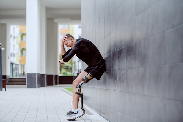Boos knappe blanke sportman met kunstbeen, leunend op de muur, hoofd vast te houden en polshorloge te kijken.