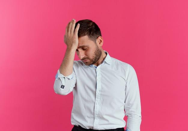 Boos knappe man legt hand op voorhoofd geïsoleerd op roze muur