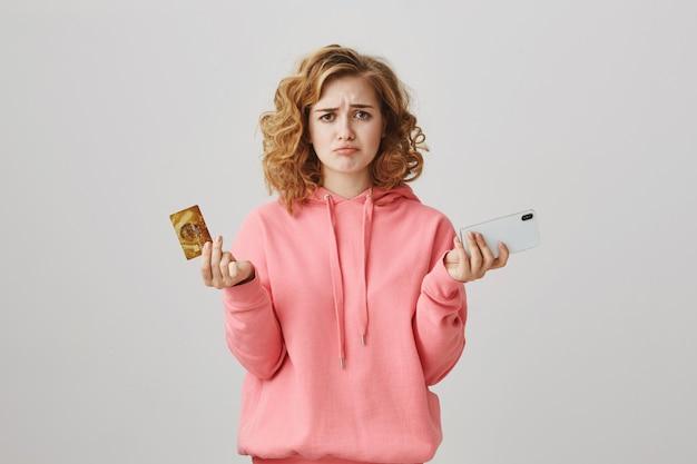 Boos krullend meisje fronsend, geld op bankrekening ontbreekt, mobiele telefoon vasthouden