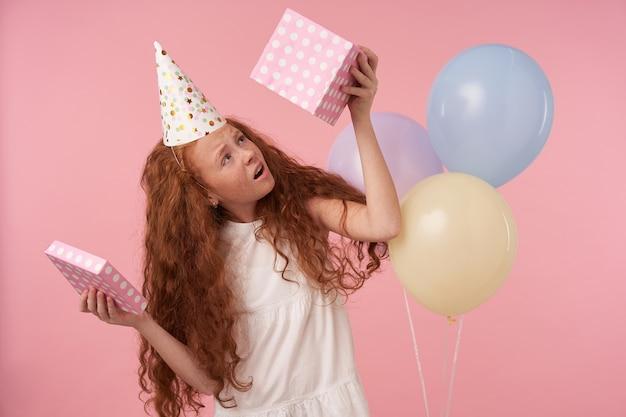 Boos krullend meisje met foxy lang haar, gekleed in witte jurk en verjaardag pet, lege huidige doos te houden en helaas naar binnen te kijken, poseren geïsoleerd over roze studio achtergrond met gekleurde ballonnen