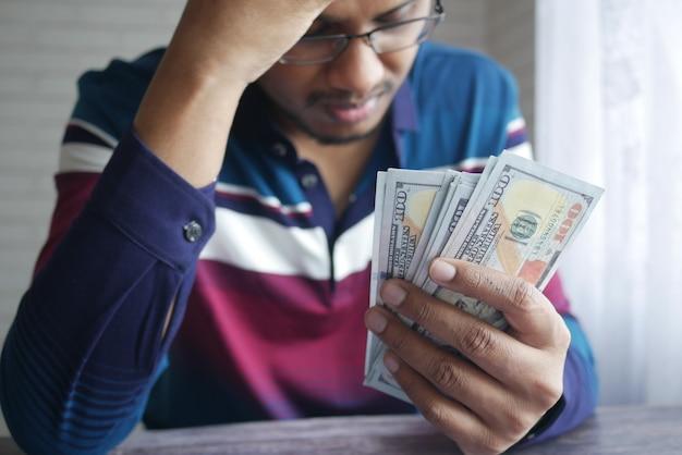 Boos man hand met ons dollar contant geld
