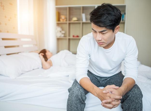 Boos man met probleem zittend op het bed na ruzie met zijn vriendin