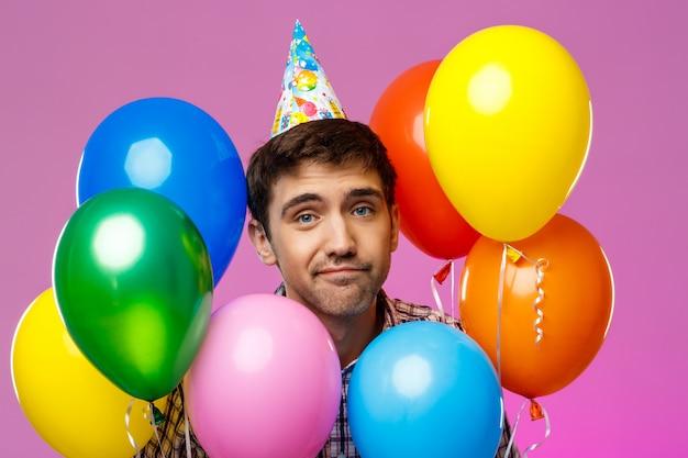 Boos man viert verjaardag, kleurrijke baloons houden over paarse muur.