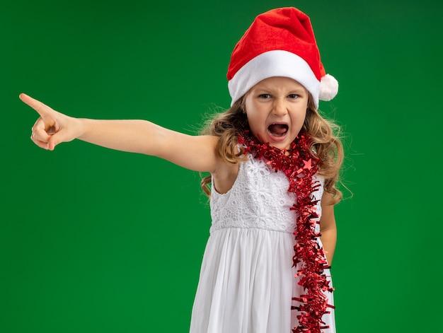 Boos meisje dat kerstmishoed met slinger op halspunten draagt aan kant die op groene achtergrond wordt geïsoleerd