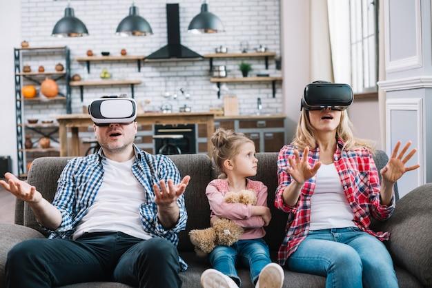 Boos meisje die haar ouders kijken terwijl moeder die virtuele werkelijkheidsglazen thuis draagt