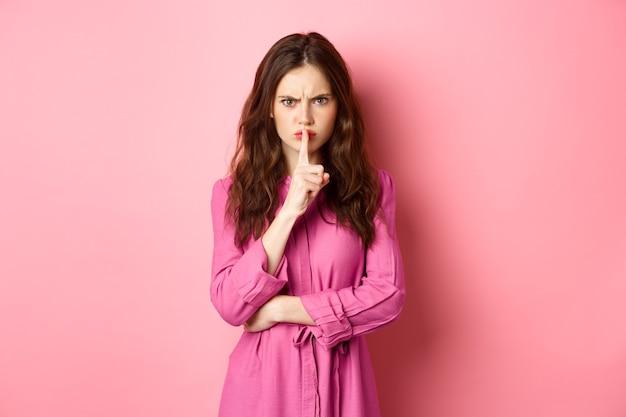 Boos meisje fronst ontevreden, zwijgt naar de camera, drukt haar vingers tegen de lippen en zegt dat ze stil moet zijn, scheldt omdat ze luid is, staande tegen een roze muur.