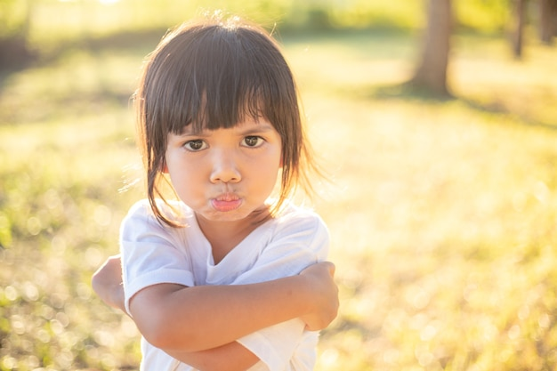 Boos meisje op tuinachtergrond, teken en gebaarconcept