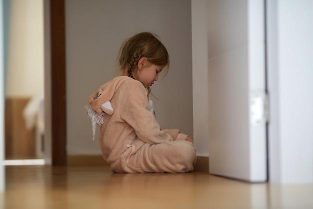 Boos meisje zittend op de vloer in de buurt van de deur