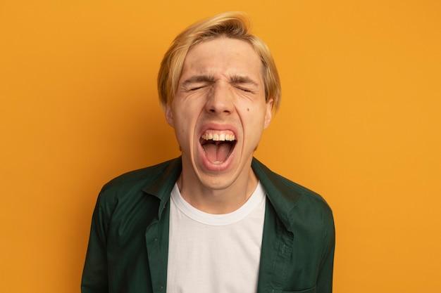 Boos met gesloten ogen jonge blonde kerel die groene t-shirt draagt