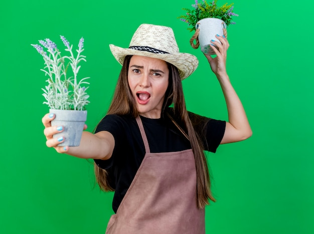 Boos mooi tuinman meisje in uniform dragen tuinieren hoed verhogen en standhouden op camera bloemen in bloempot geïsoleerd op groene achtergrond