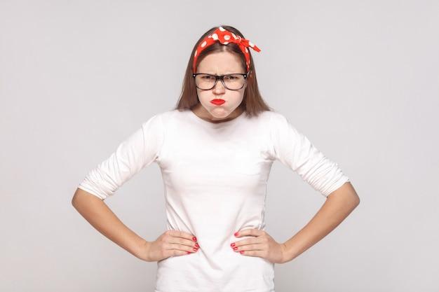 Boos nadenkend, opgeheven handen. portret van mooie emotionele jonge vrouw in wit t-shirt met sproeten, zwarte bril, rode lippen en hoofdband. indoor studio opname, geïsoleerd op lichtgrijze achtergrond.