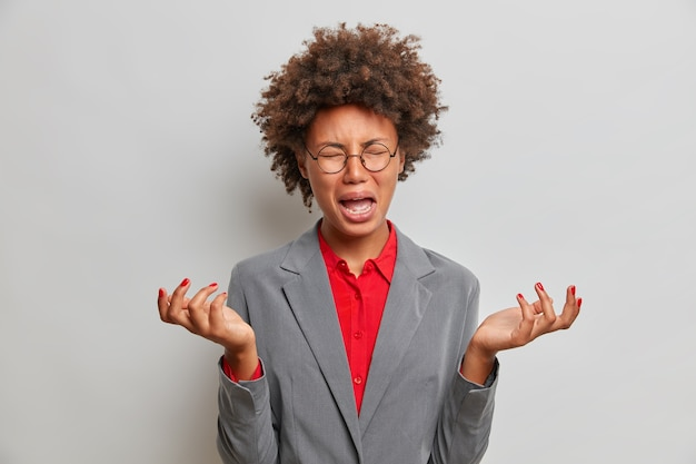 Boos neerslachtige etnische leraar spreidt handpalmen, huilt van depressie, heeft problemen op het werk, gekleed in formele kleding, drukt negatieve emoties uit