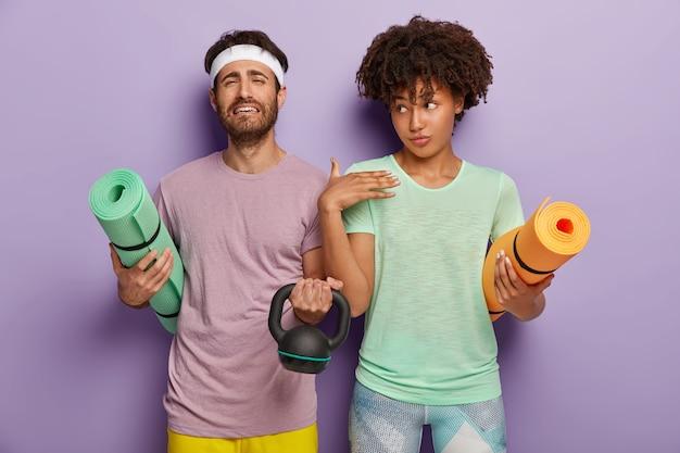 Boos ongeschoren man houdt opgerolde karemat vast, heft gewicht, gaat sporten, staan naast elkaar tegen een paarse achtergrond, gekleed in t-shirts, hebben fitnesstraining. mensen, sport, motivatie
