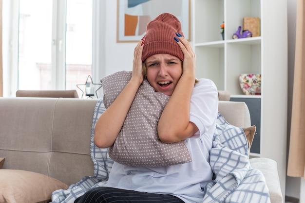 Boos ongezonde jonge vrouw in warme muts met deken die er onwel en ziek uitziet en lijdt aan verkoudheid en griep die een kussen vasthoudt en er bezorgd uitziet en het hoofd aanraakt zittend op de bank in een lichte woonkamer