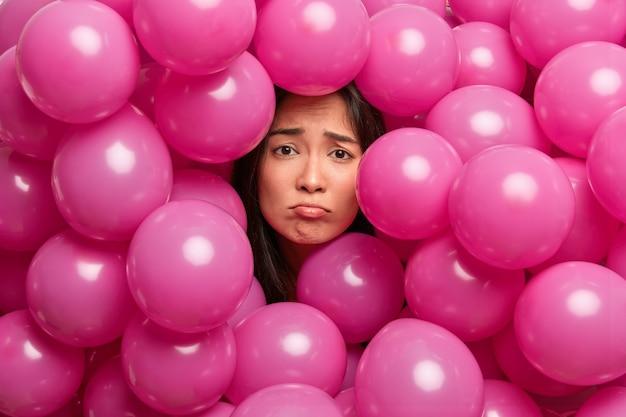 Boos ontevreden ellendige aziatische vrouw omringd met roze ballonnen heeft een slecht humeur. saai verjaardagsfeestje. negatieve emoties concept