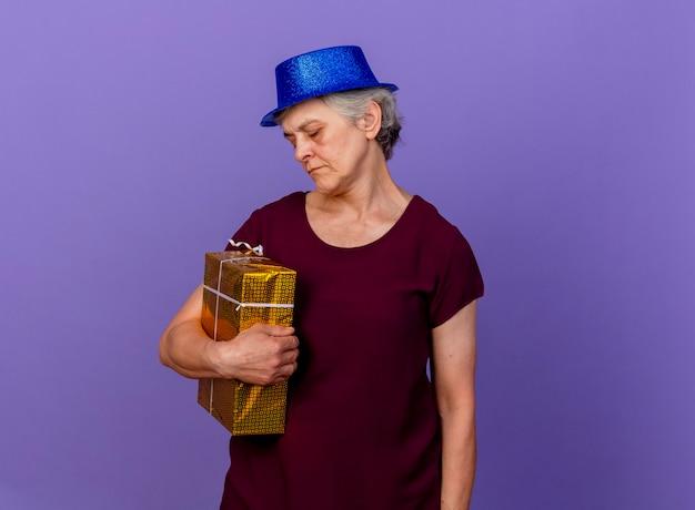 Boos oudere vrouw met feestmuts houdt en kijkt naar geschenkdoos geïsoleerd op paarse muur met kopie ruimte