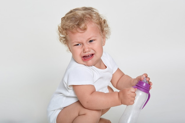 Boos peuter huilen terwijl squats tegen witte ruimte, kind wil drinken, houdt lege sippy cup