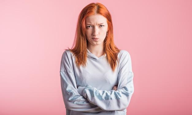 Boos roodharige meisje met gekruiste armen in de studio op een roze achtergrond