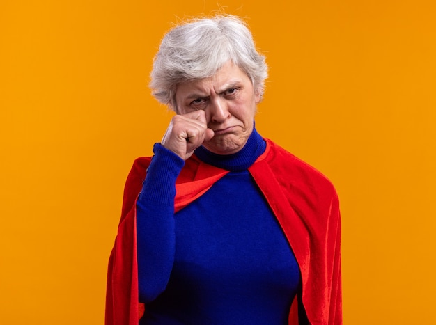 Boos senior vrouw superheld dragen rode cape camera kijken met droevige uitdrukking wrijven ogen