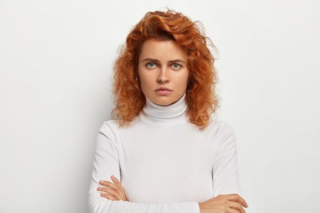 Boos sombere gember vrouw staat met gevouwen armen, mokkend en fronsend, boos op iemand, kijkt hatelijk naar camera