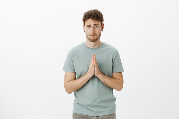 Boos sombere schattige kerel met borstelharen in t-shirt en oorbellen, handen vasthoudend in gebed en droevige glimlach maken terwijl hij om gunst vraagt, wanhopig zijn