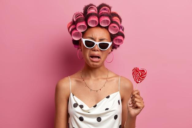 Boos sombere vrouw draagt haarkrulspelden, huilt met ontevreden uitdrukking, maakt zich klaar voor vakantie, maakt kapsel, poseert met lekker snoep op stok, draagt zonnebril en vrijetijdskleding