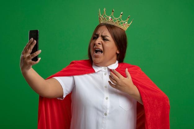 Boos superheldwijfje van middelbare leeftijd die kroon dragen die en telefoon bekijken die op groene achtergrond wordt geïsoleerd