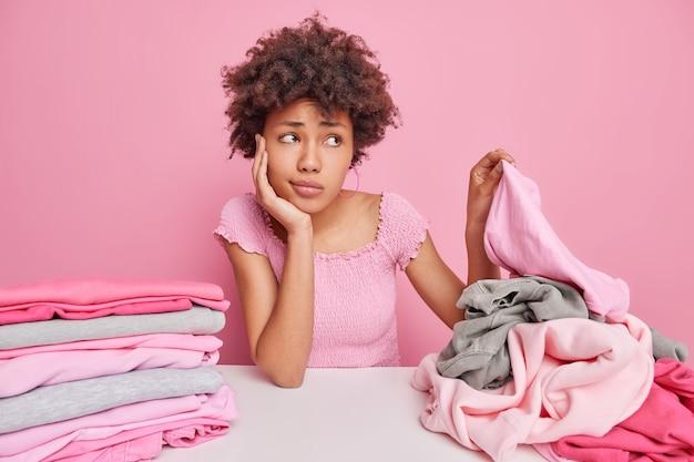 Boos triest afro-amerikaanse huisvrouw plukt kleren van stapel plooien wasgoed na het wassen heeft vermoeide ontevredenheid expressie zit aan tafel geïsoleerd over roze