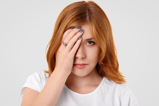 Boos triest vrouwtje bedekt de helft van het gezicht na ruzie met vriend