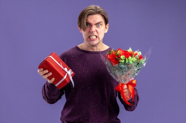 Boos uitziende camera jonge kerel op valentijnsdag met geschenkdoos met boeket geïsoleerd op blauwe achtergrond