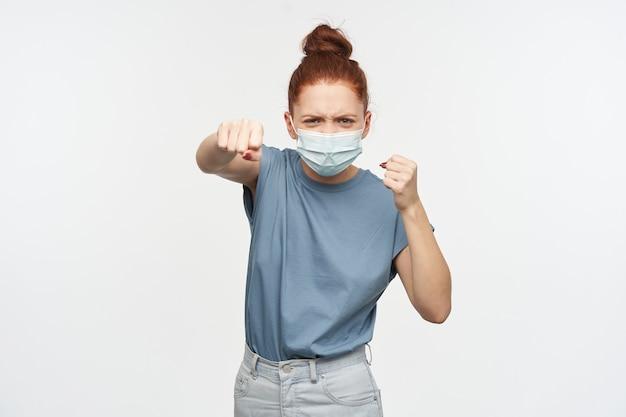 Boos uitziende vrouw, meisje met gemberhaar verzameld in een knot. het dragen van een blauw t-shirt, een spijkerbroek en een beschermend gezichtsmasker. bal haar vuisten en stoot. geïsoleerd over witte muur