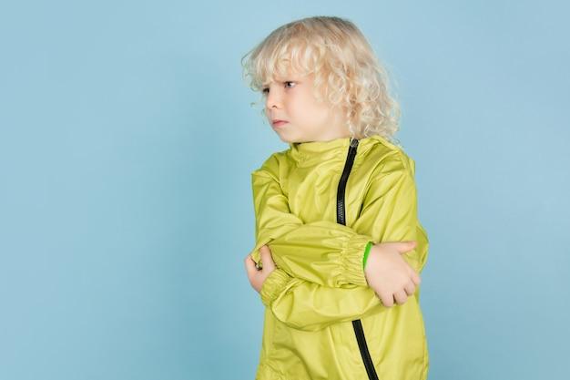 Boos, verdrietig. portret van mooie kaukasische kleine jongen geïsoleerd op blauwe muur. blond krullend mannelijk model. concept van gezichtsuitdrukking, menselijke emoties, kindertijd
