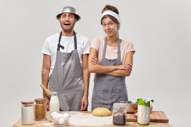 Boos vermoeide man huilt en verveelt zich, draagt een schort en kom op het hoofd, wil vrouw niet helpen met het bakken van gebak of taart, samen poseren in de keukenruimte bij de tafel met ingrediënten. bakkerij concept