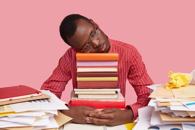 Boos vermoeide zwarte man doet dutje op stapel boeken, slaapt na een hele nacht studeren, voorbereid op examens
